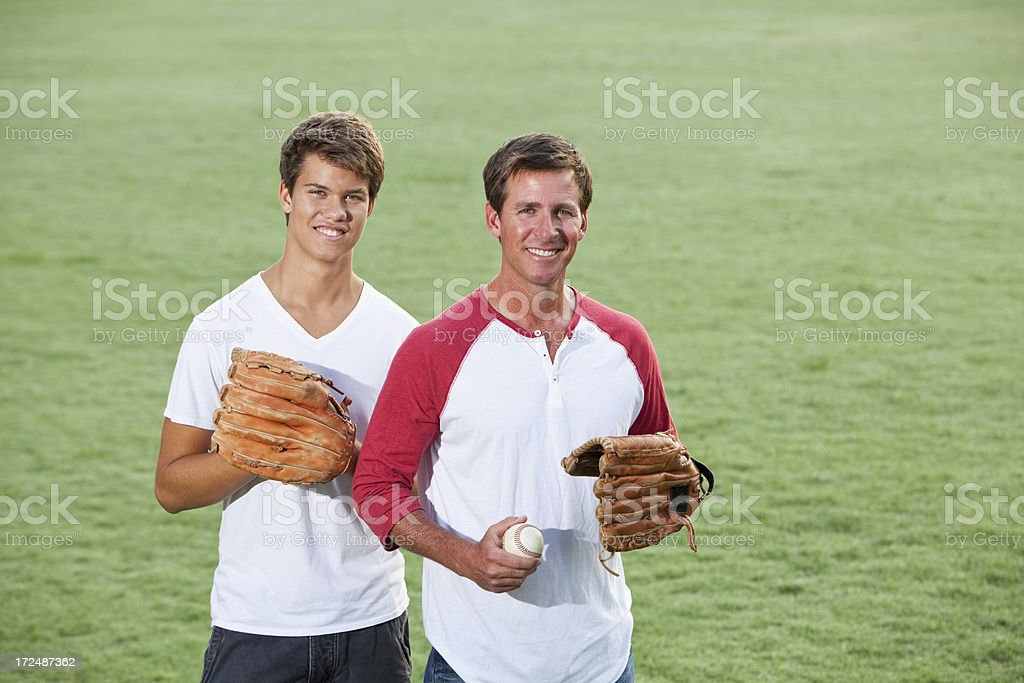 Father and teenage son playing baseball royalty-free stock photo