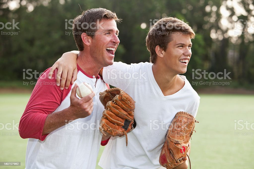 Father and teenage son playing baseball stock photo