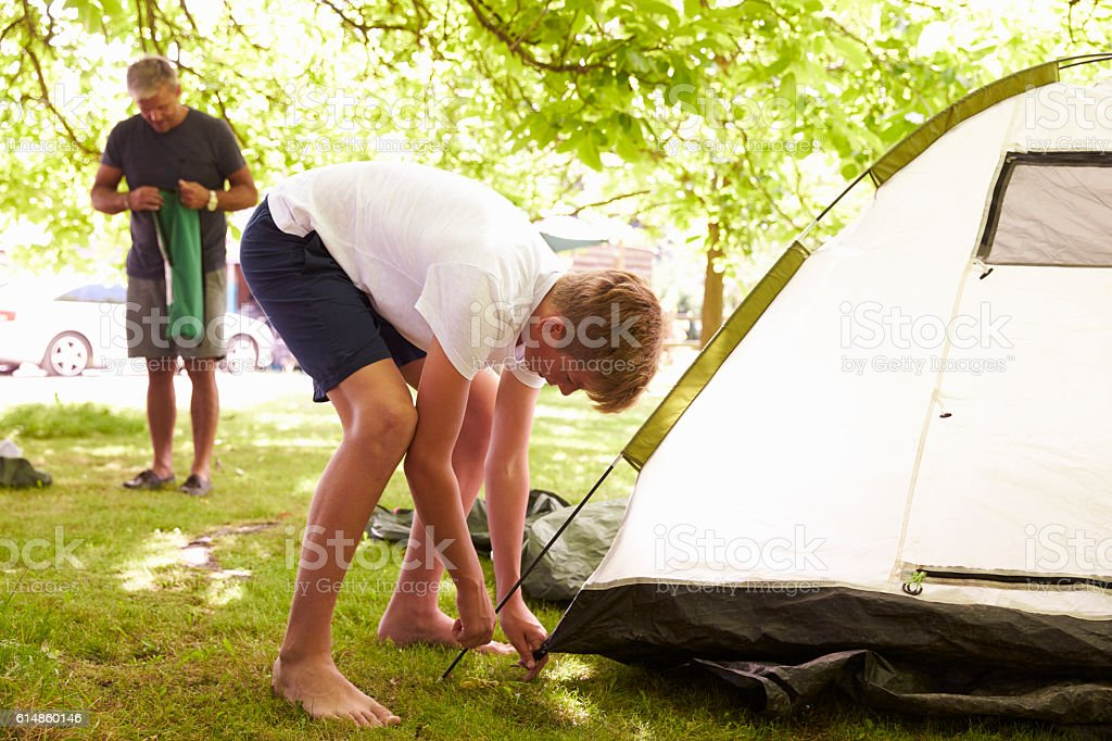 Father And Teenage Son Putting Up Tent On Camping Trip stock photo