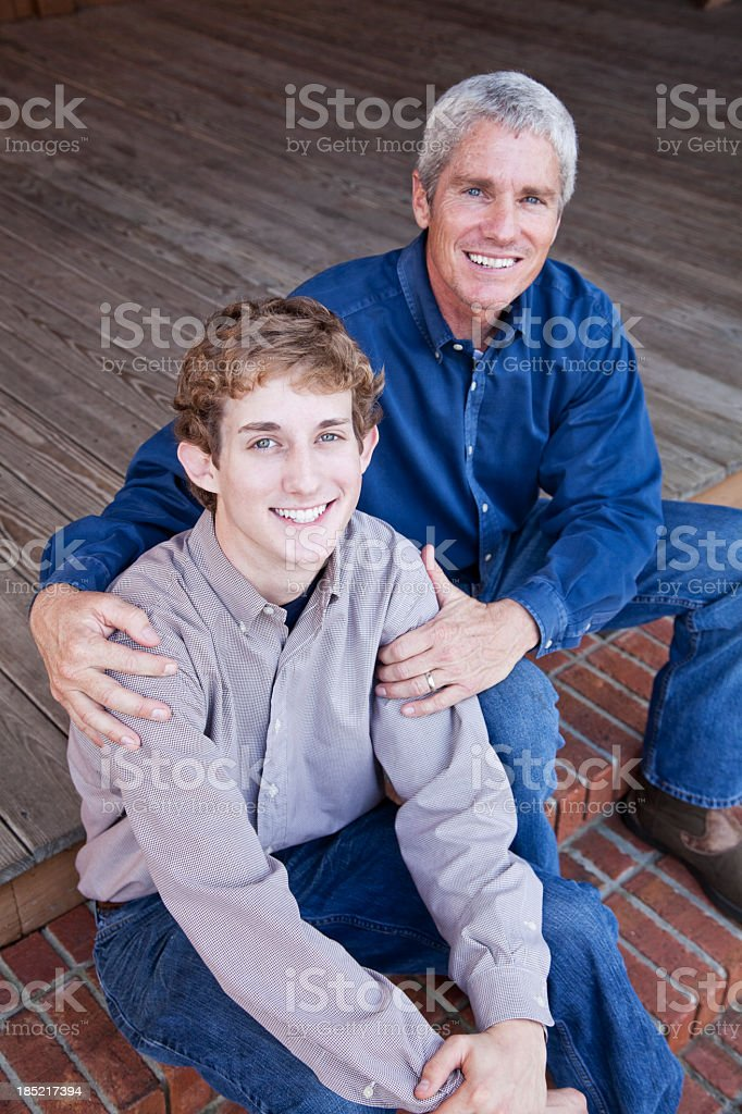 Father and teenage son sitting on porch steps royalty-free stock photo