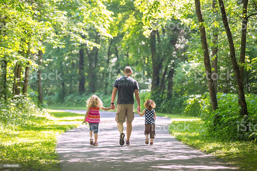 Father And Two Daughters Walking Through Woods at Park stock photo