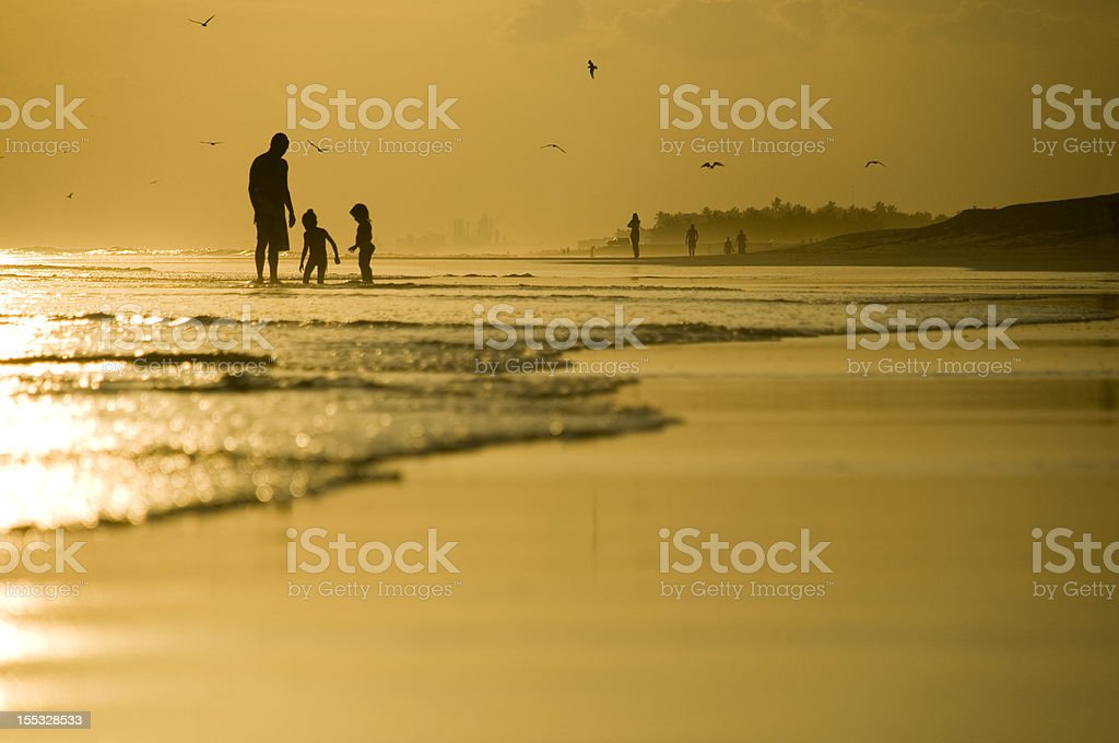 Father and two kids playing on the beach royalty-free stock photo