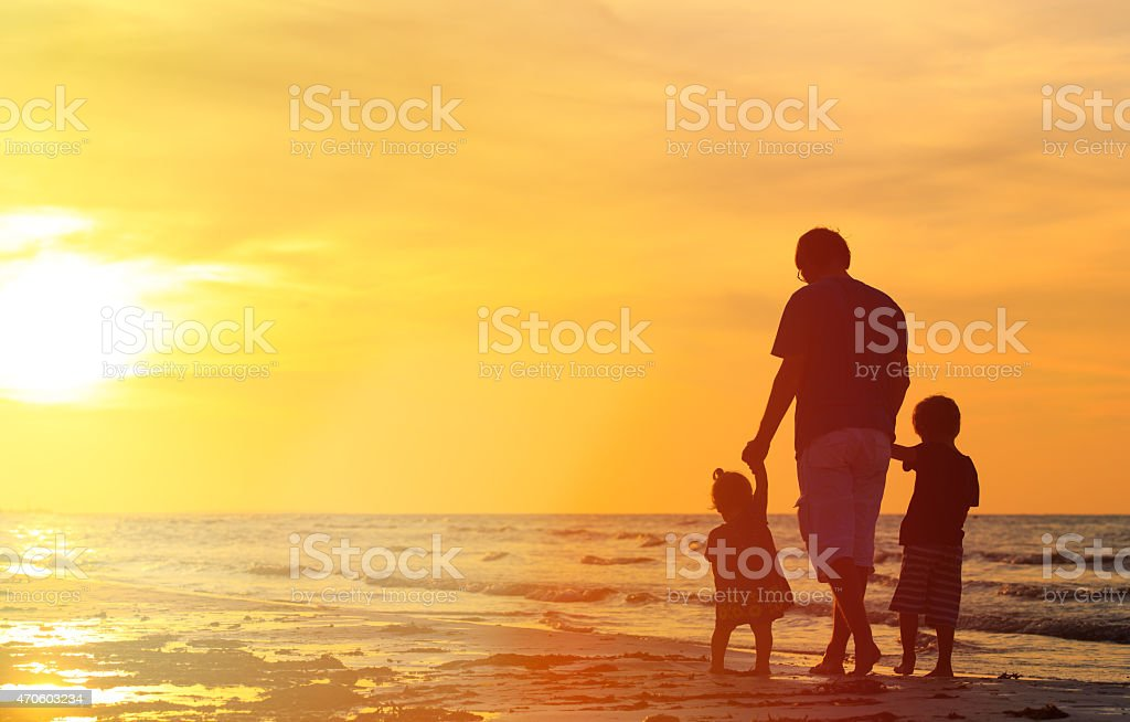 father and two kids walking at sunset stock photo