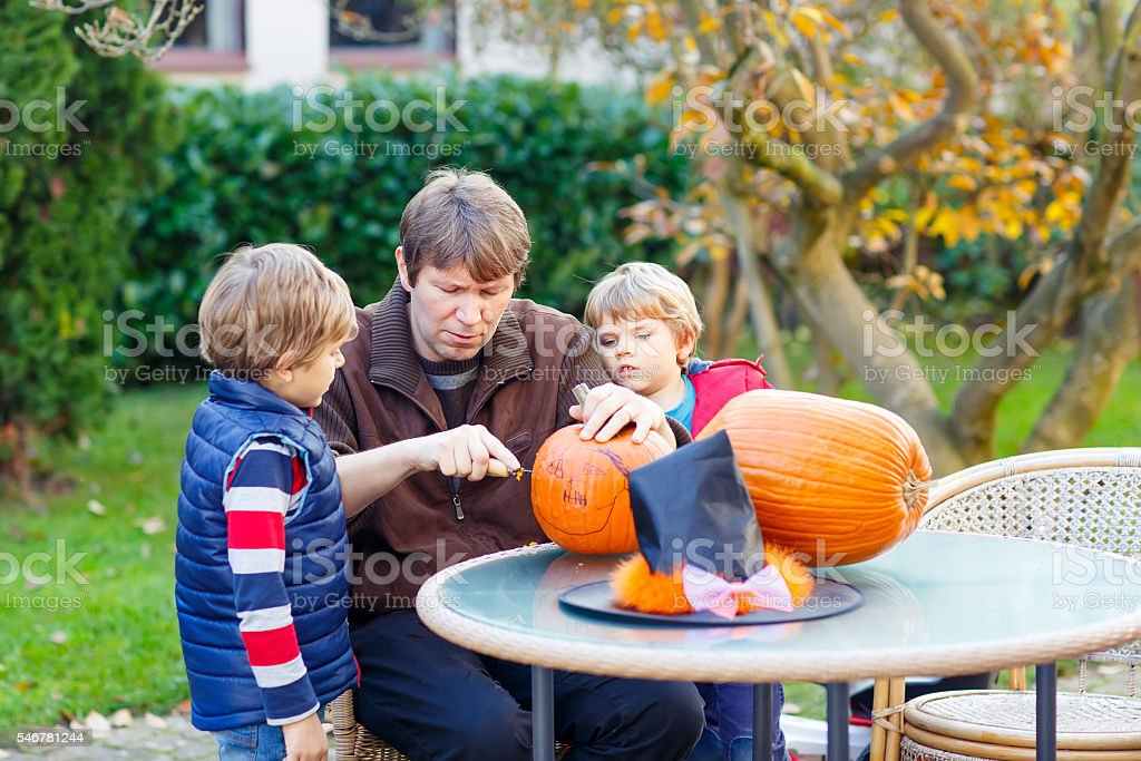 Father and two little kid boys making halloween pumpkin stock photo