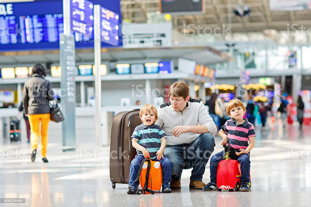 Father and two little kids at the airport, traveling together stock photo