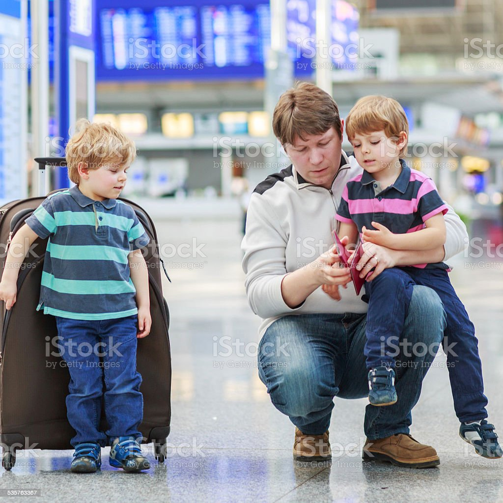 Father and two little sibling boys at the airport stock photo