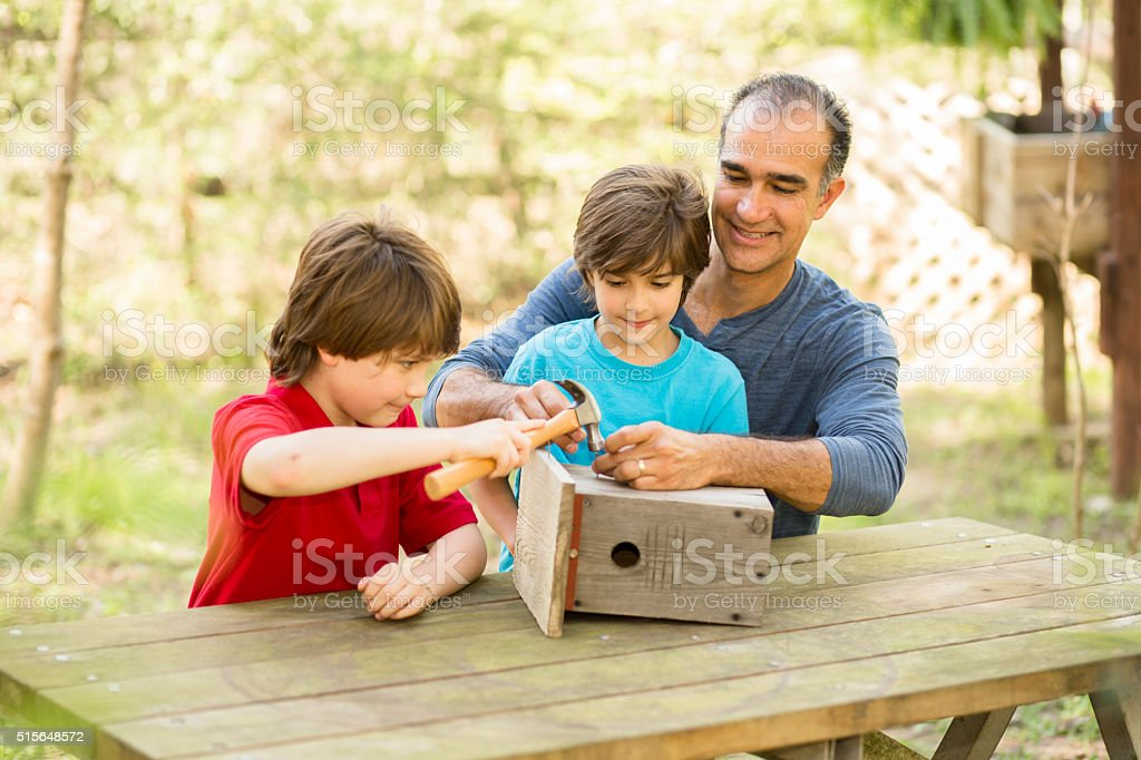 Father and two sons building birdhouse outdoors. Family time! stock photo