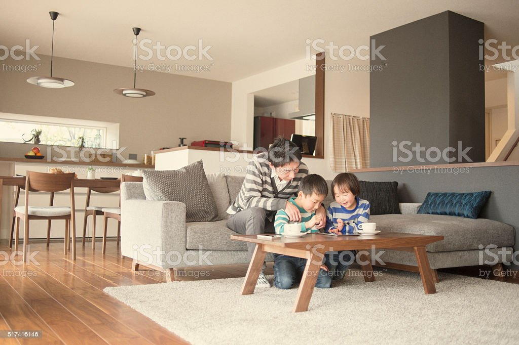 Father and two sons playing with a digital tablet together stock photo