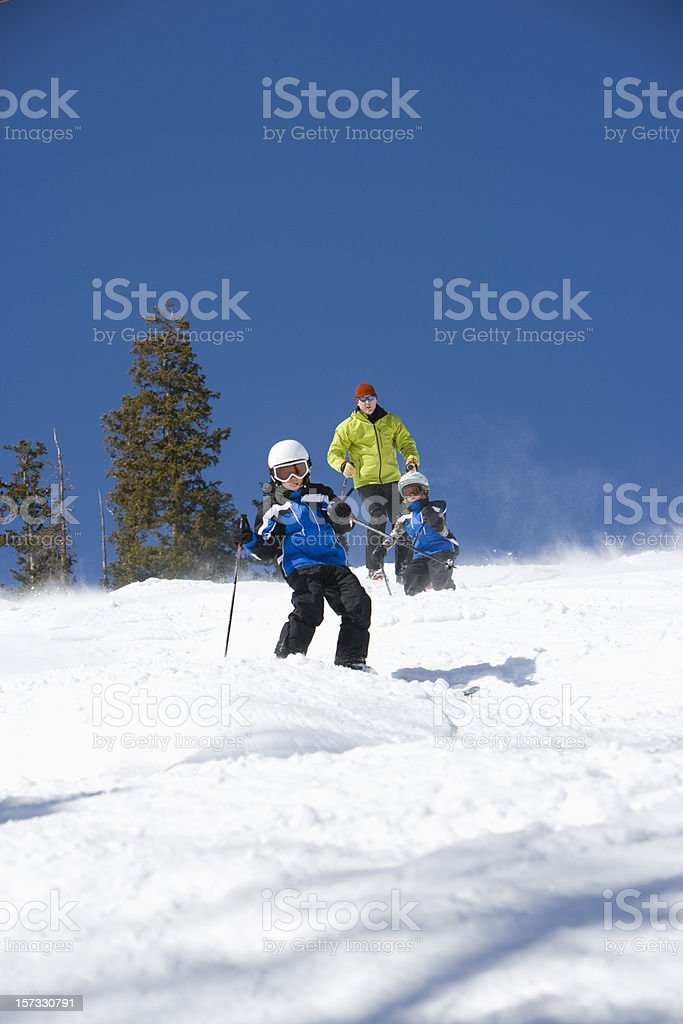 Father and two sons skiing together royalty-free stock photo