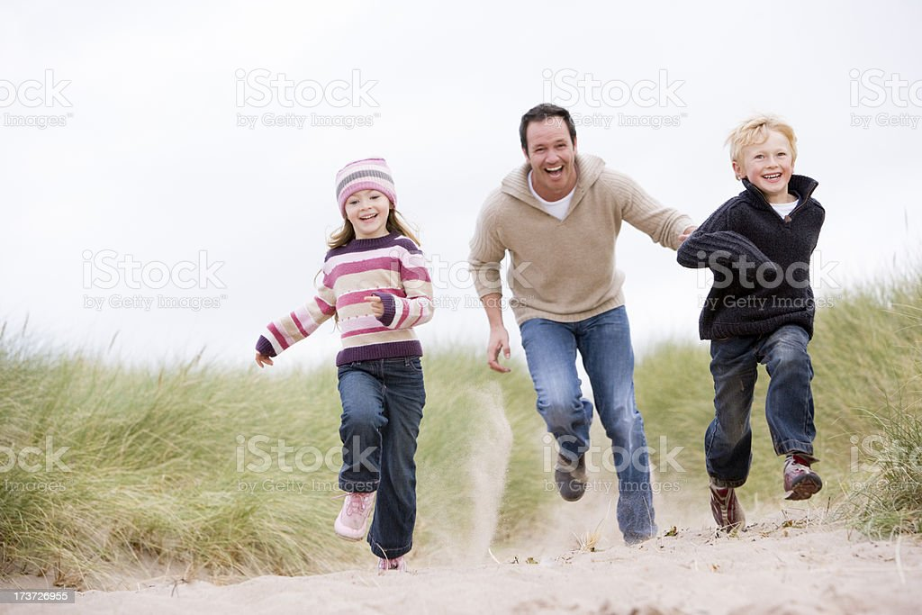 Father and two young children running at beach smiling royalty-free stock photo