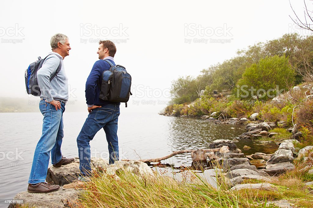 Father and young adult son standing by a lake stock photo