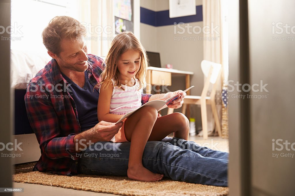 Father and young daughter reading together stock photo
