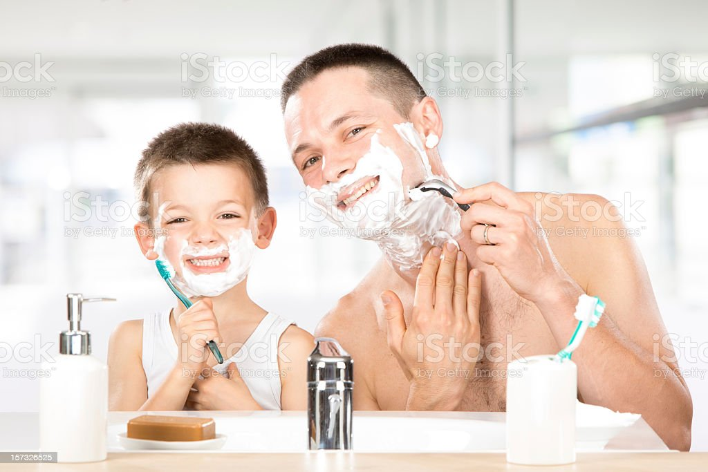 Father and young son shaving together stock photo