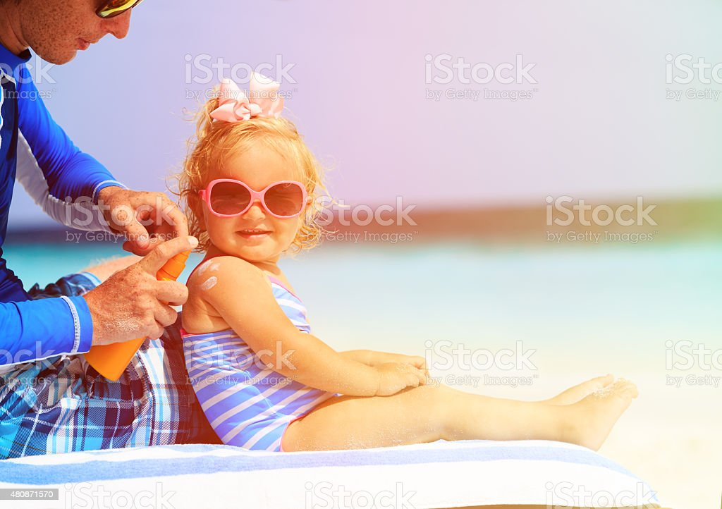 father applying sunblock cream on daughters shoulder stock photo