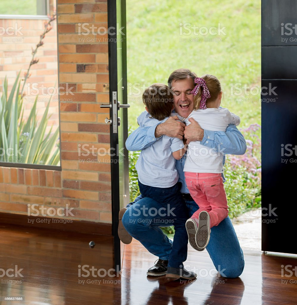 Father arriving home and hugging his kids stock photo