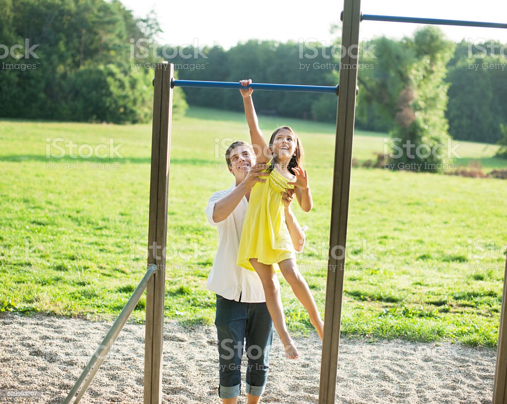 Father assising daughter at bars at playground stock photo