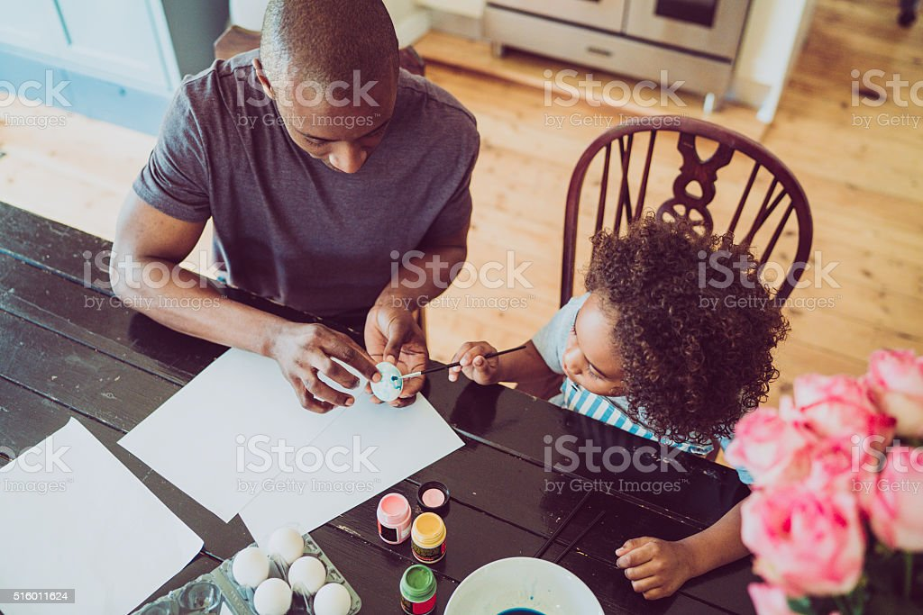 Father assisting girl in painting Easter egg at home stock photo