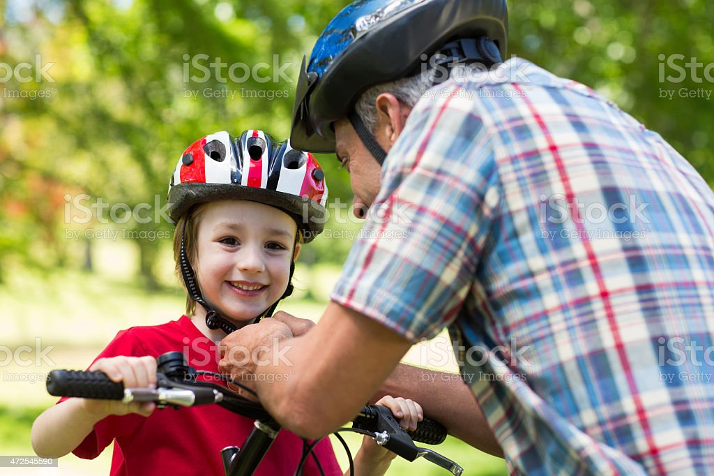 Father attaching his sons cycling helmet stock photo