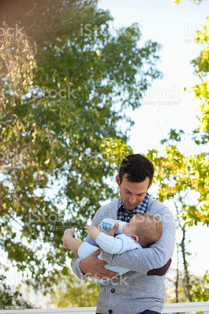 Father bottle feeding baby outdoors royalty-free stock photo
