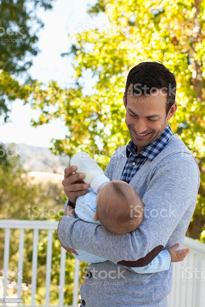 Father bottle feeding son outdoors royalty-free stock photo