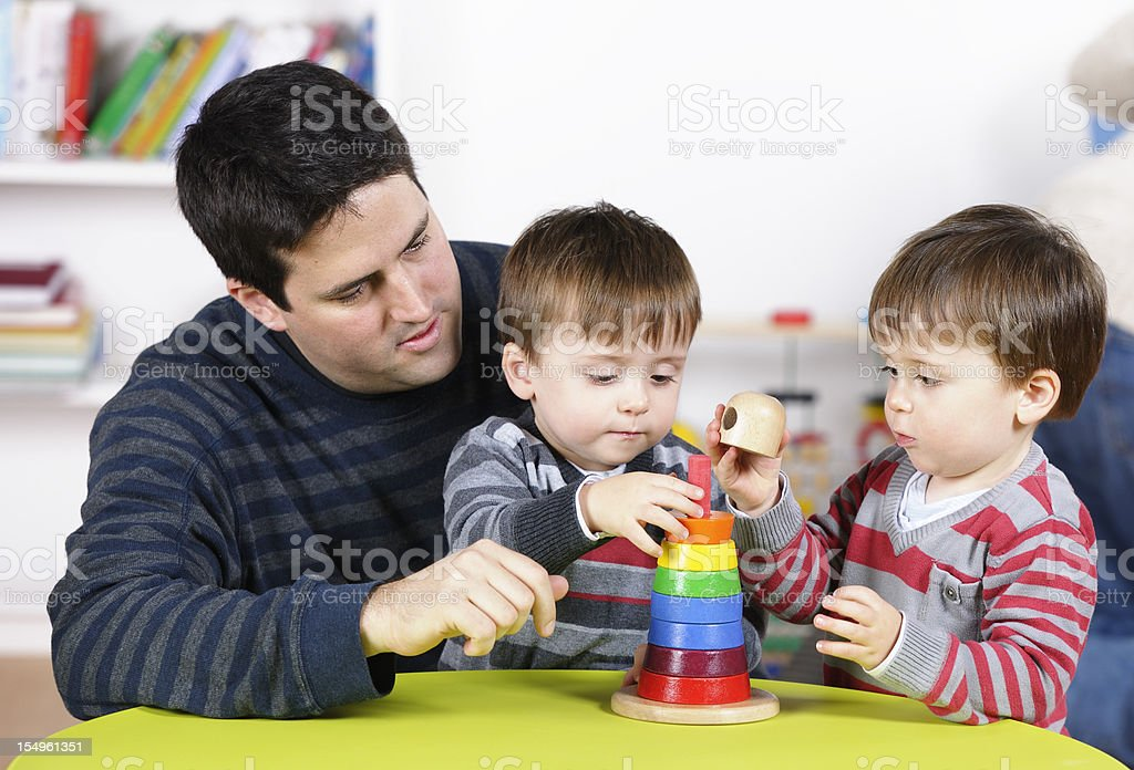 Father/ Carer Supervises Twin Boys Using Developmental Toy At Playtime royalty-free stock photo