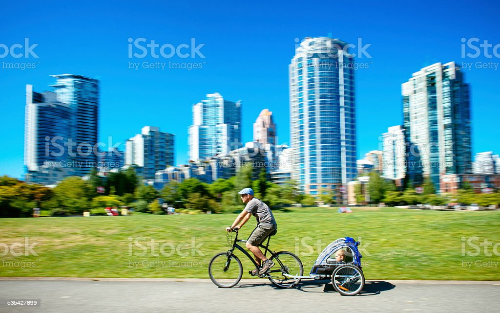 Father carries son in bicycle trailer in Vancouver Canada stock photo