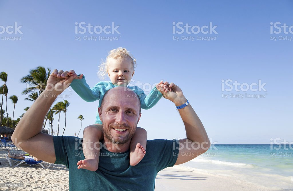 Father carrying baby boy at the beach royalty-free stock photo