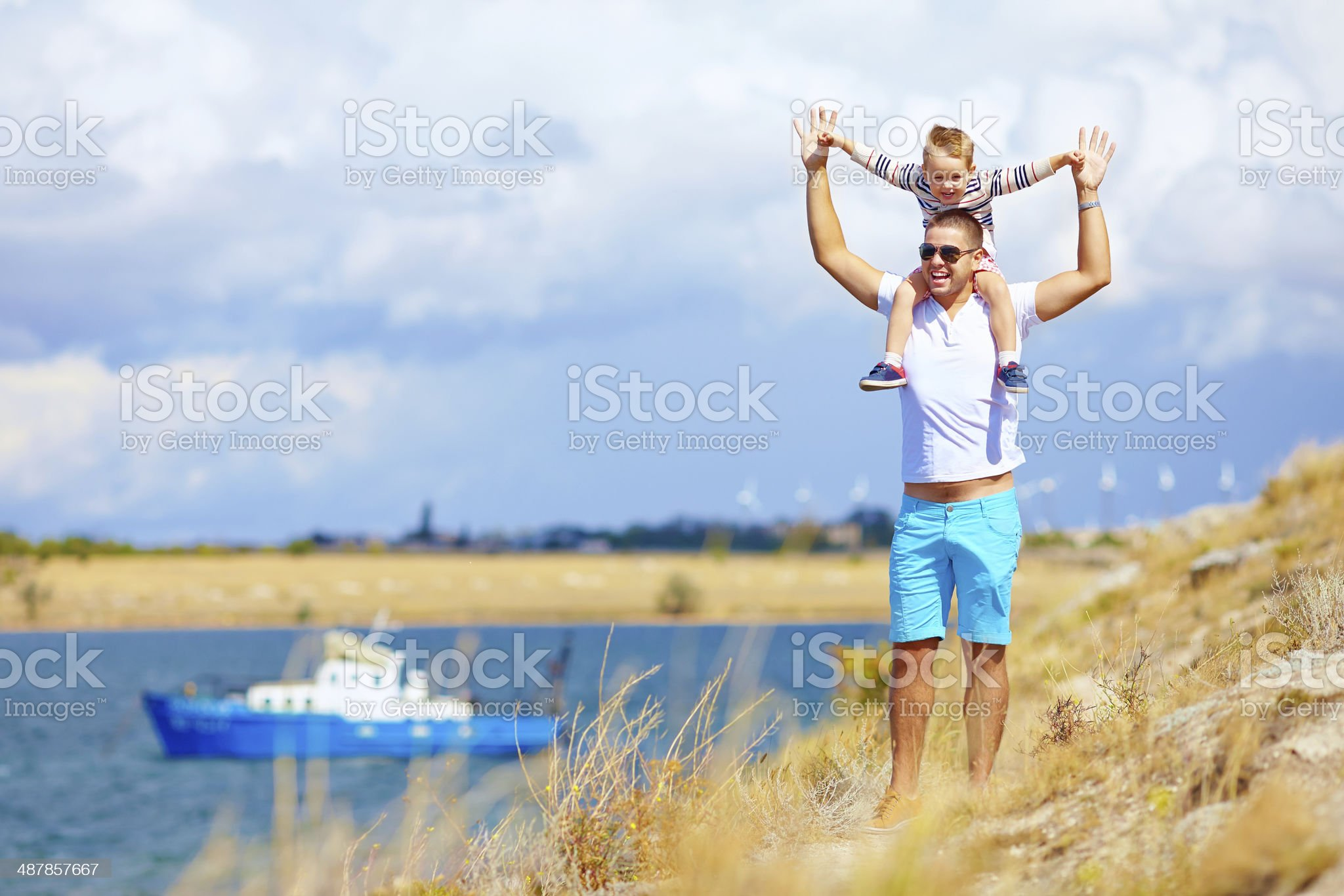 Father carrying child on shoulders at seaside royalty-free stock photo
