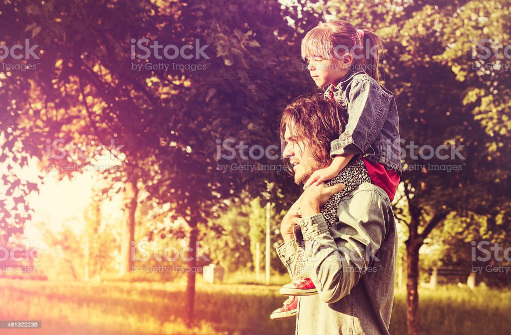 Father carrying daughter on his shoulders in nature at sunset stock photo