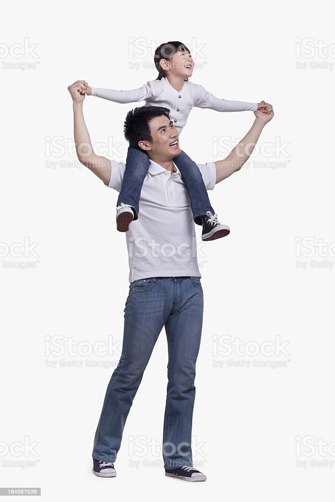 Father carrying daughter on his shoulders, studio shot stock photo