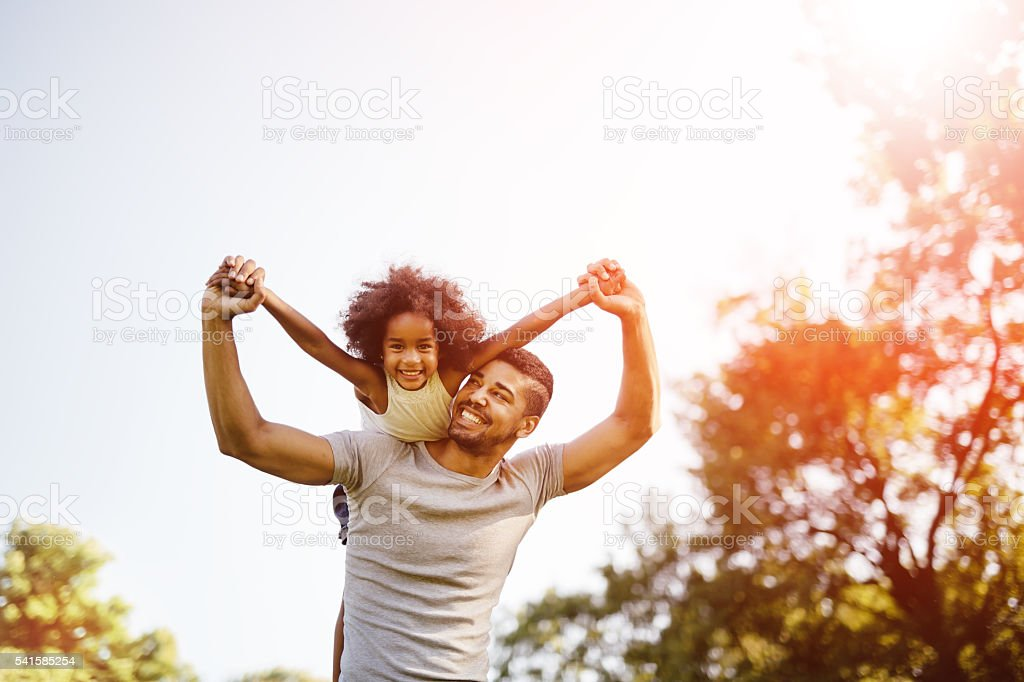 Father carrying daughter piggyback stock photo