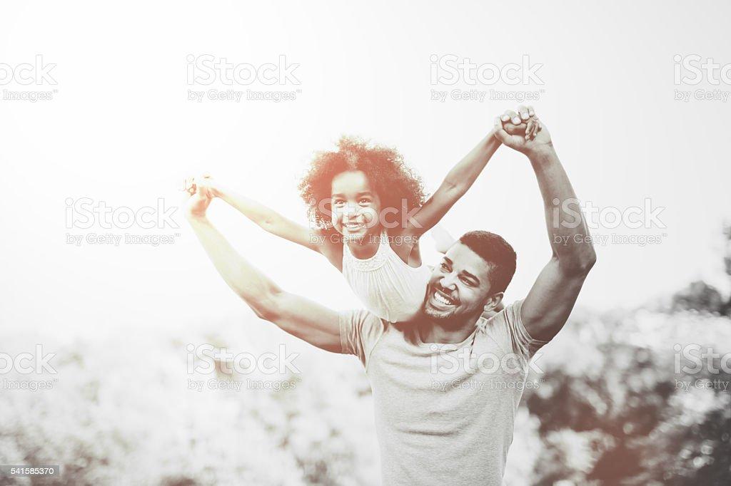 Father carrying daughter piggyback stock photo