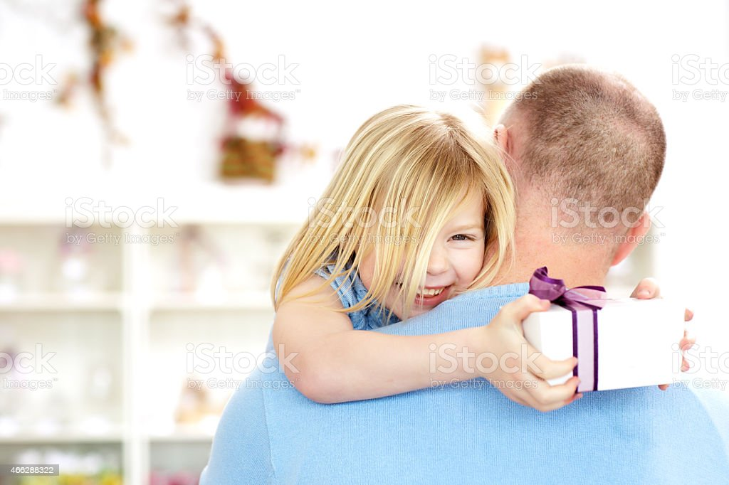 father carrying happy daughter holding gift box stock photo