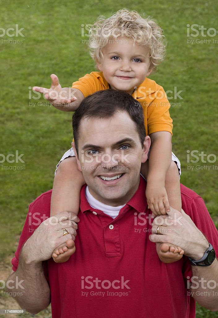 Father carrying happy son on shoulders stock photo