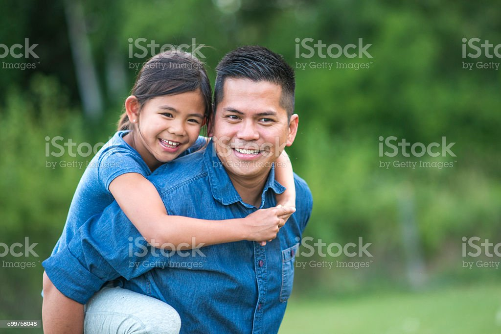 Father Carrying his Daughter on his Back stock photo