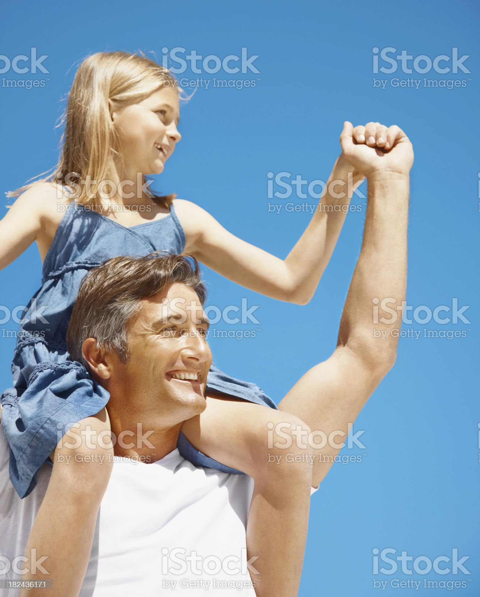 Father carrying his daughter on shoulders against blue sky royalty-free stock photo