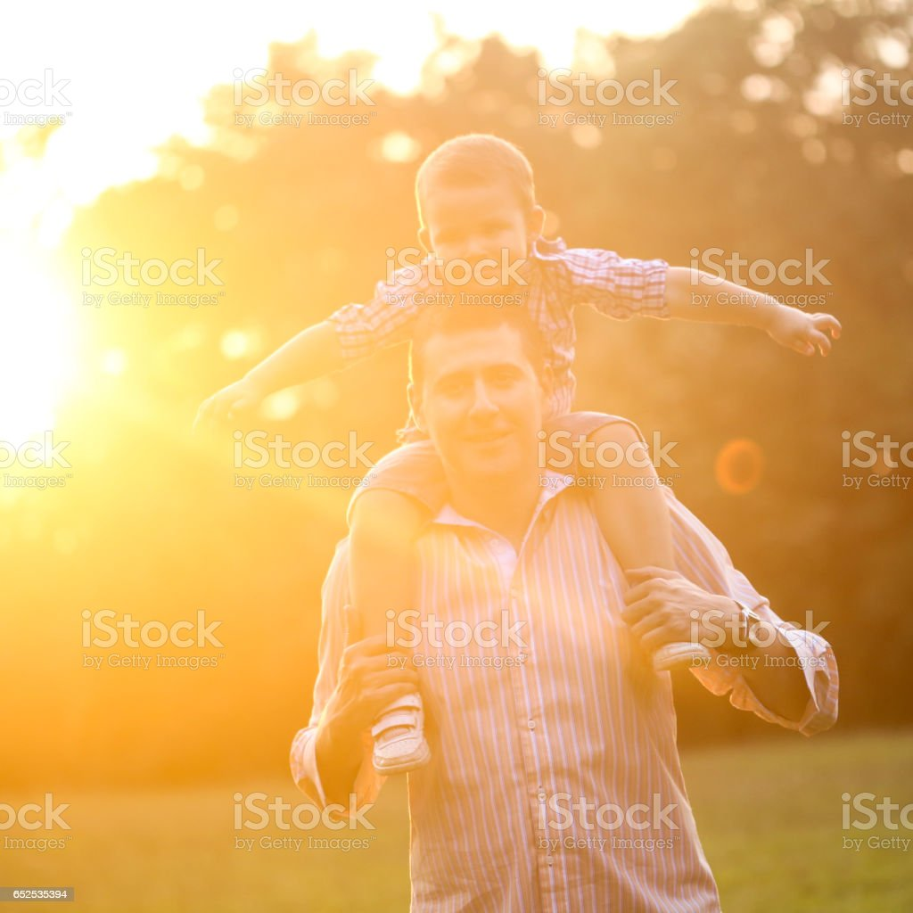 Father carrying his son on his shoulders stock photo
