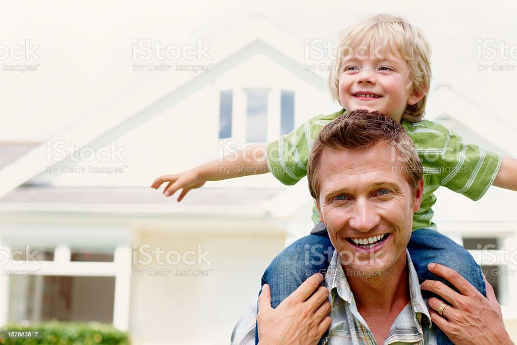 Father carrying his son on shoulders in front of house stock photo