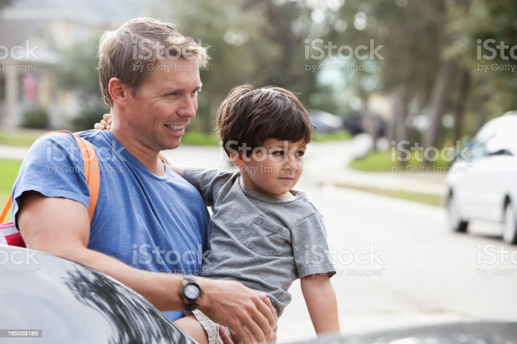 Father carrying little boy, standing outside car stock photo