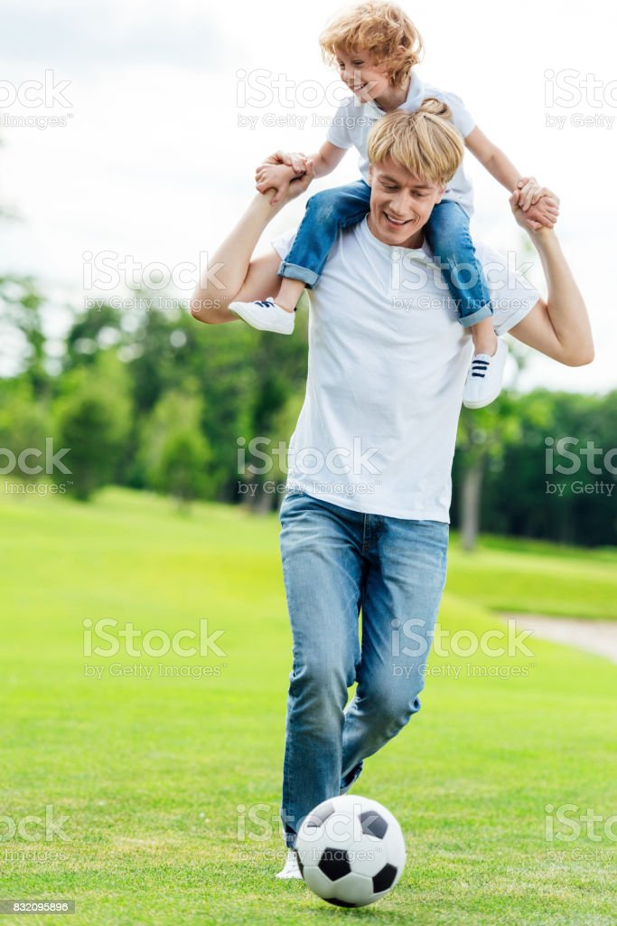 father carrying little son on shoulders while playing soccer in park stock photo
