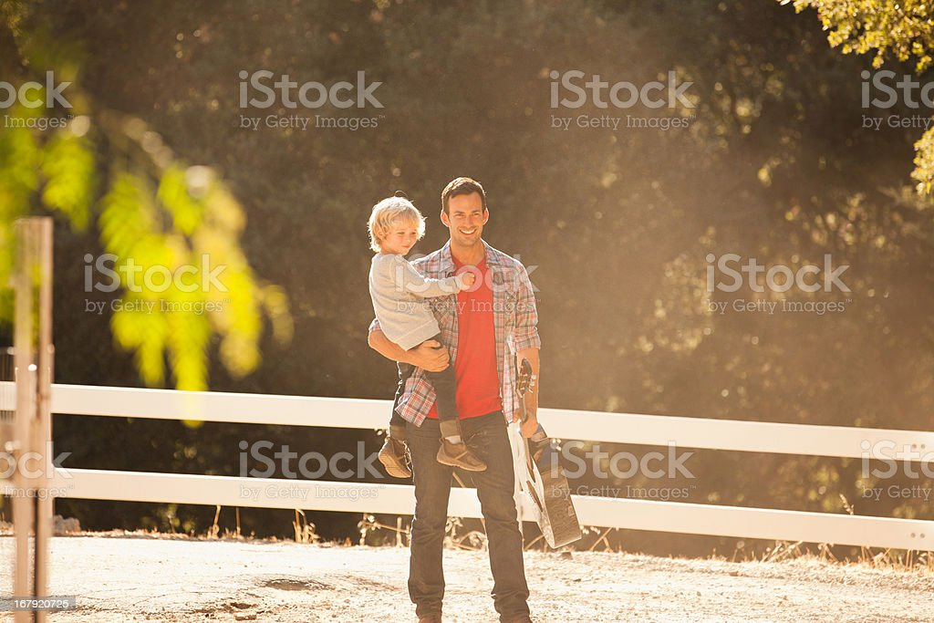 Father carrying son and guitar outdoors royalty-free stock photo