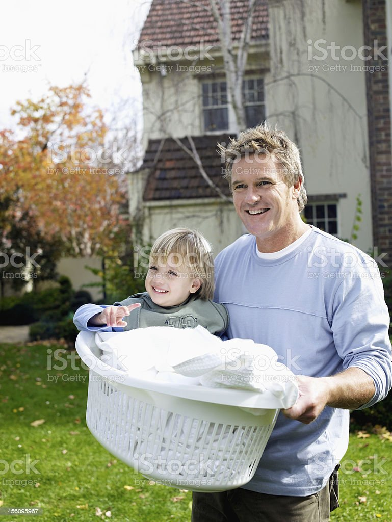 Father Carrying Son in Laundry Basket stock photo