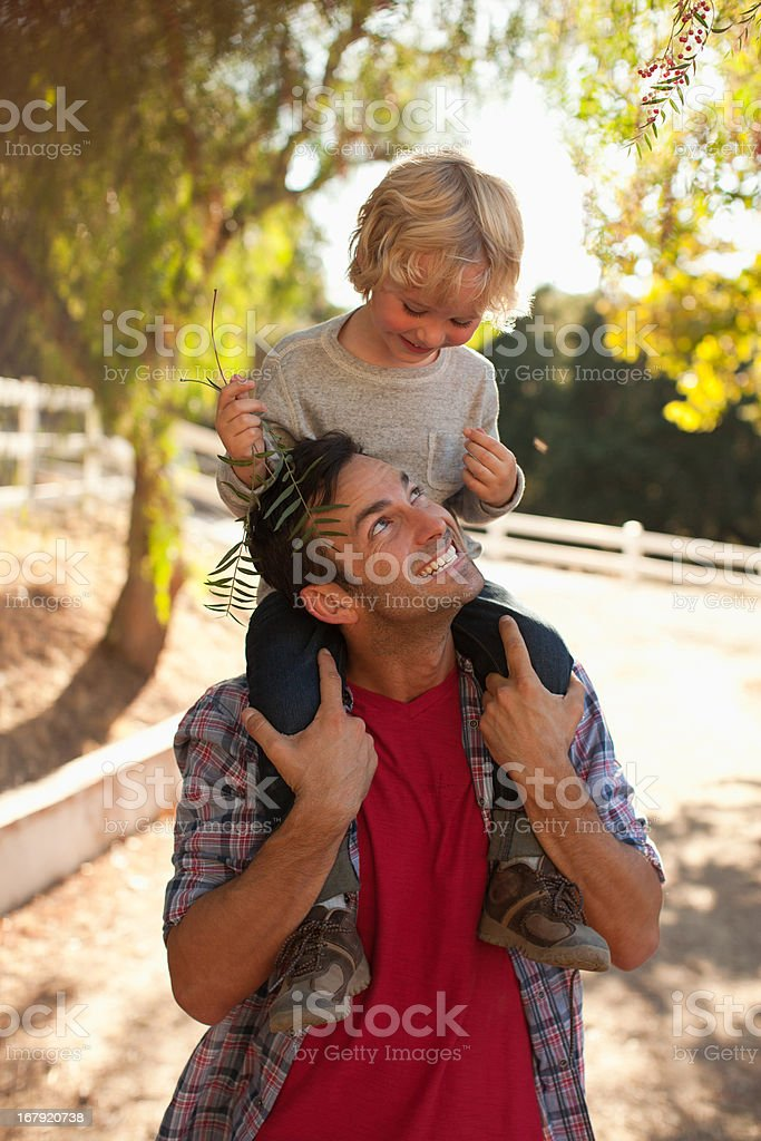 Father carrying son on shoulders royalty-free stock photo