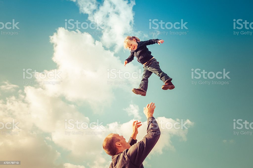 Father catching girl falling from cloudy sky stock photo