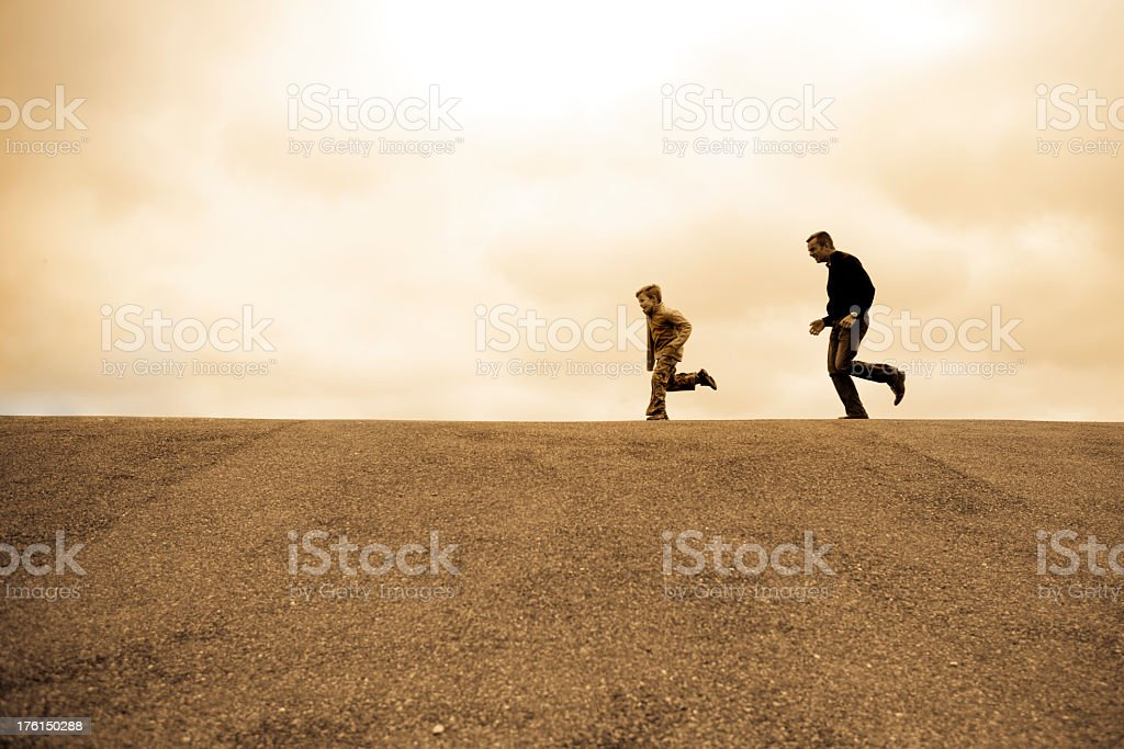 Father chasing son outdoors and having fun stock photo