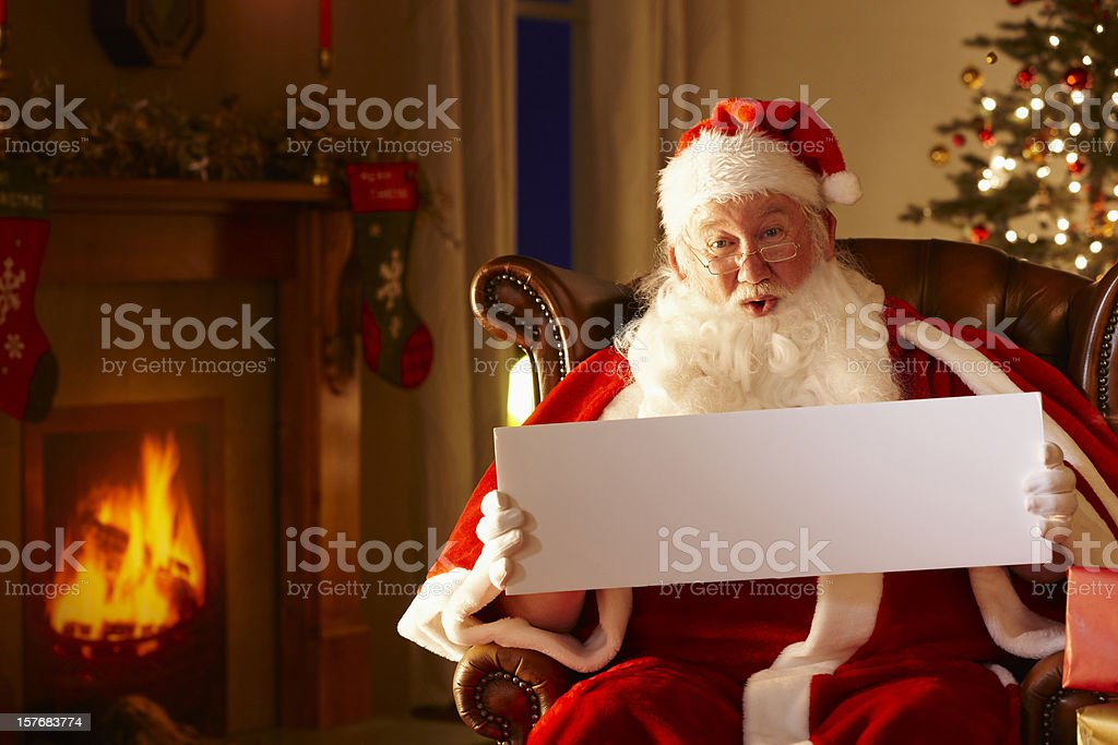 Father Christmas Sitting holding wide whiteboard royalty-free stock photo
