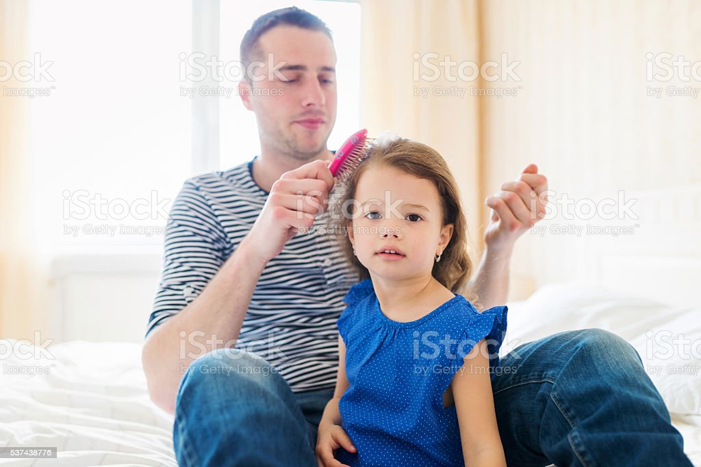 Father combing hair of his daughter in the morning stock photo