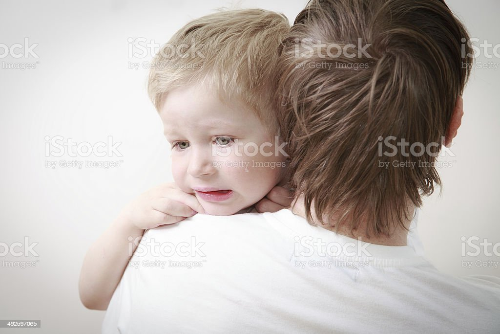 father comforting son in tears stock photo
