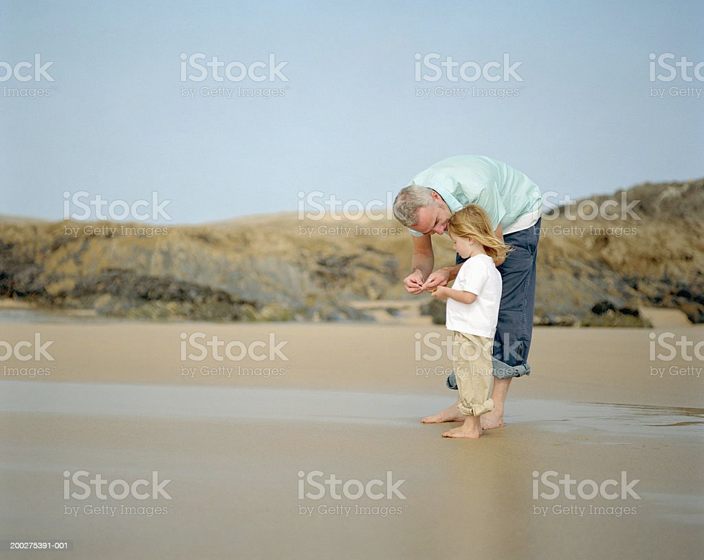 Father crouching by daughter (2-4) on beach stock photo