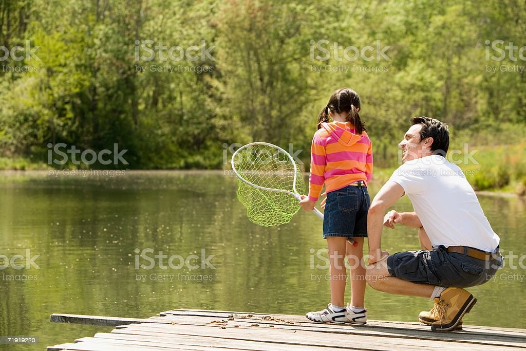 Father crouching next to daughter on jetty, holding fishing net royalty-free stock photo